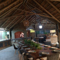 Lapa with a big dining table, indoor braai and lounge with DSTV.