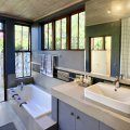 Duminy: Bedroom 1 bathroom with tub and outdoor shower with views to a milkwood grove and mountains