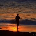 Fisherman at sunrise at Ansteys Beach