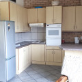 Blue Sea Unit 4. Full kitchen with island style seating. Fridge, microwave oven, kettle, toaster, iron.