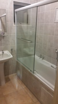 Second bathroom with a shower in the bath and a separate toilet